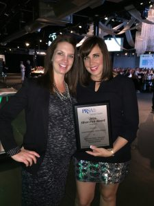 Rhiannon and Michelle holding their PRSA Colorado Silver Pick Award