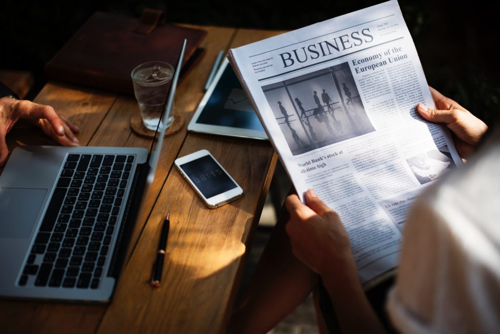 Laptop and business section of newspaper